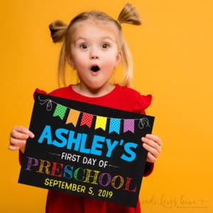girl holding chalkboard first day of school sign
